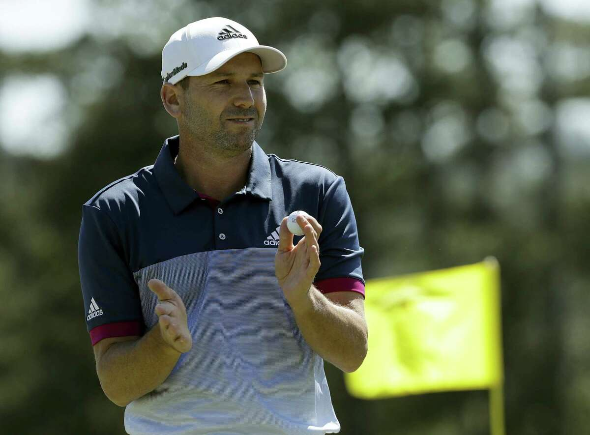 Sergio Garcia claps after putting on the 18th green.