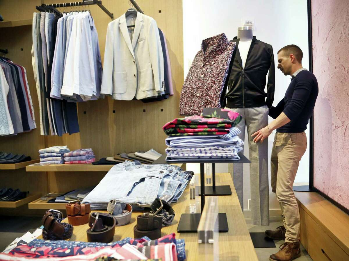 In this Monday, March 20, 2017, file photo, Bonobos manager Stephen Lusardi arranges clothing at the brand's Guideshop, in New York's Financial District. The U.S. government issues the March jobs report, Friday, April 7, 2017.