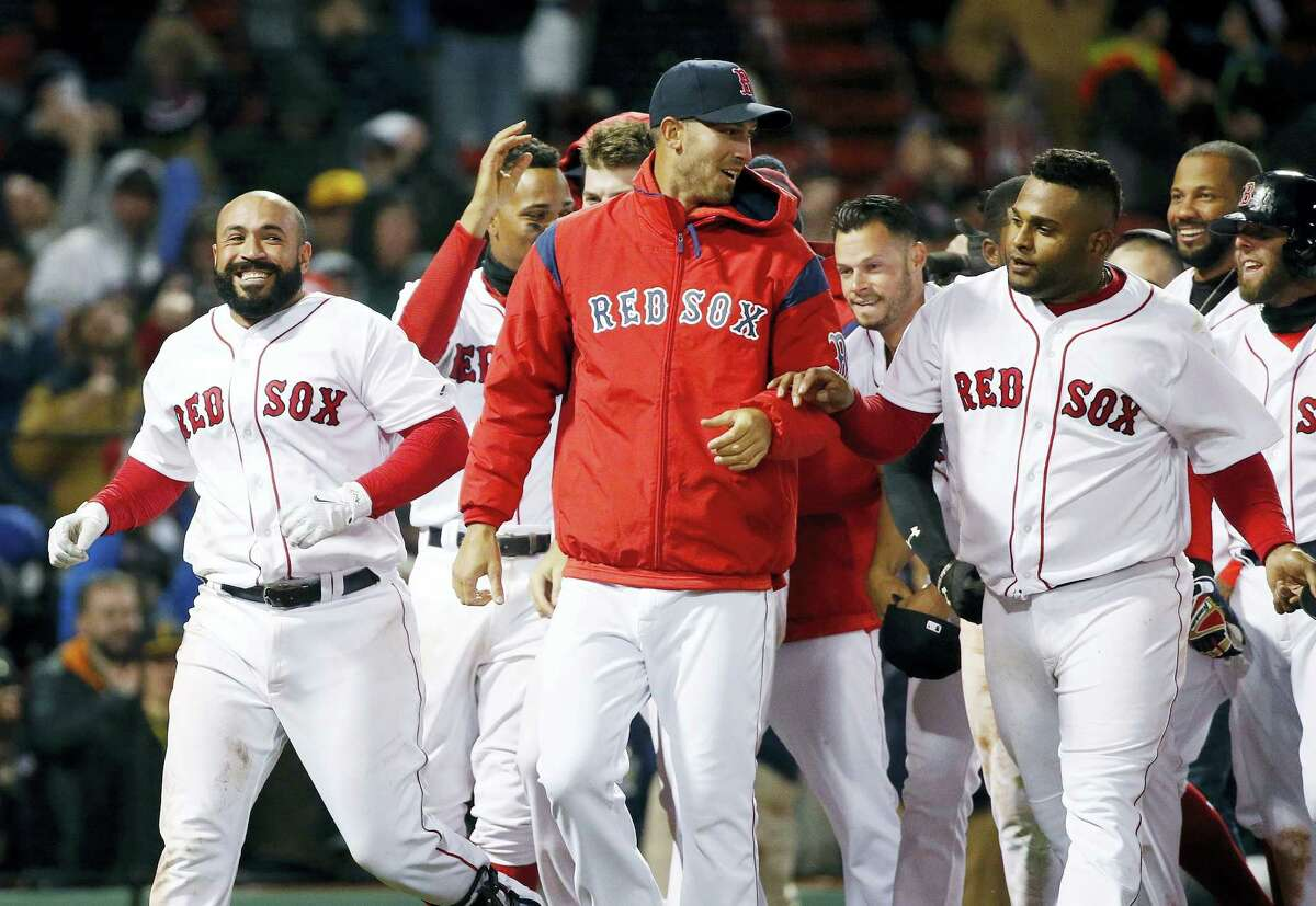 Boston Red Sox's Sandy Leon, left, celebrates with teammates including Rick Porcello, center, and Pablo Sandoval, right, after hitting a three-run home run during the 12th inning of a baseball game against the Pittsburgh Pirates in Boston, Wednesday. The Red Sox won 3-0.