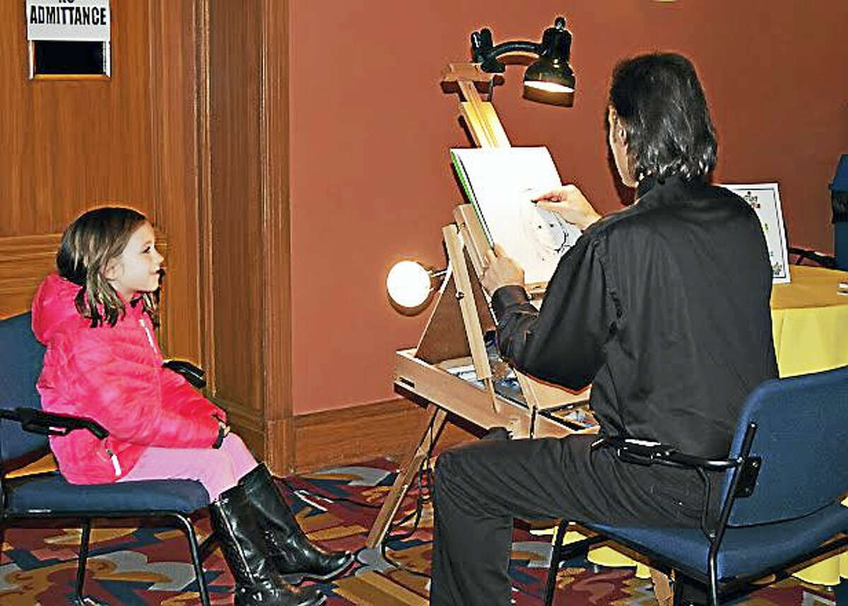 Caricature artist Bill Hernandez creates art for a young participant at last year's KidsPlay museum event.