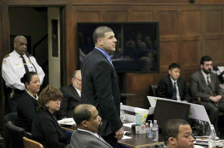 Former New England Patriots tight end Aaron Hernandez, center, stands when asked to do so by defense attorney Jose Baez, not shown, as Baez makes closing arguments Thursday in Boston. Photo: Steven Senne — The Associated Press  / Copyright 2017 The Associated Press. All rights reserved.