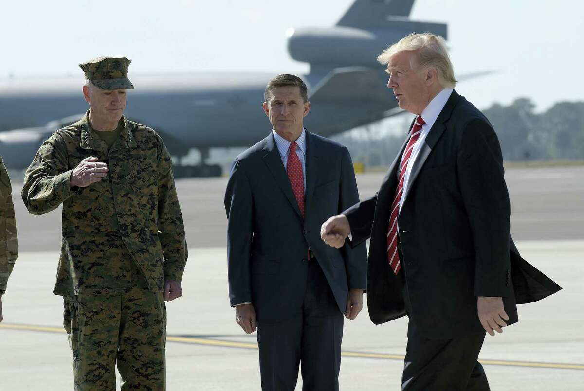 In this Monday, Feb. 6, 2017 photo, President Donald Trump passes Joint Chiefs Chairman Gen. Joseph Dunford, left, and National Security Adviser Michael Flynn as he arrives via Air Force One at MacDill Air Force Base in Tampa, Fla. A top White House aide sidestepped repeated chances Sunday, Feb. 12, to publicly defend Flynn following reports that he engaged in conversations with a Russian diplomat about U.S. sanctions before Trump's inauguration.