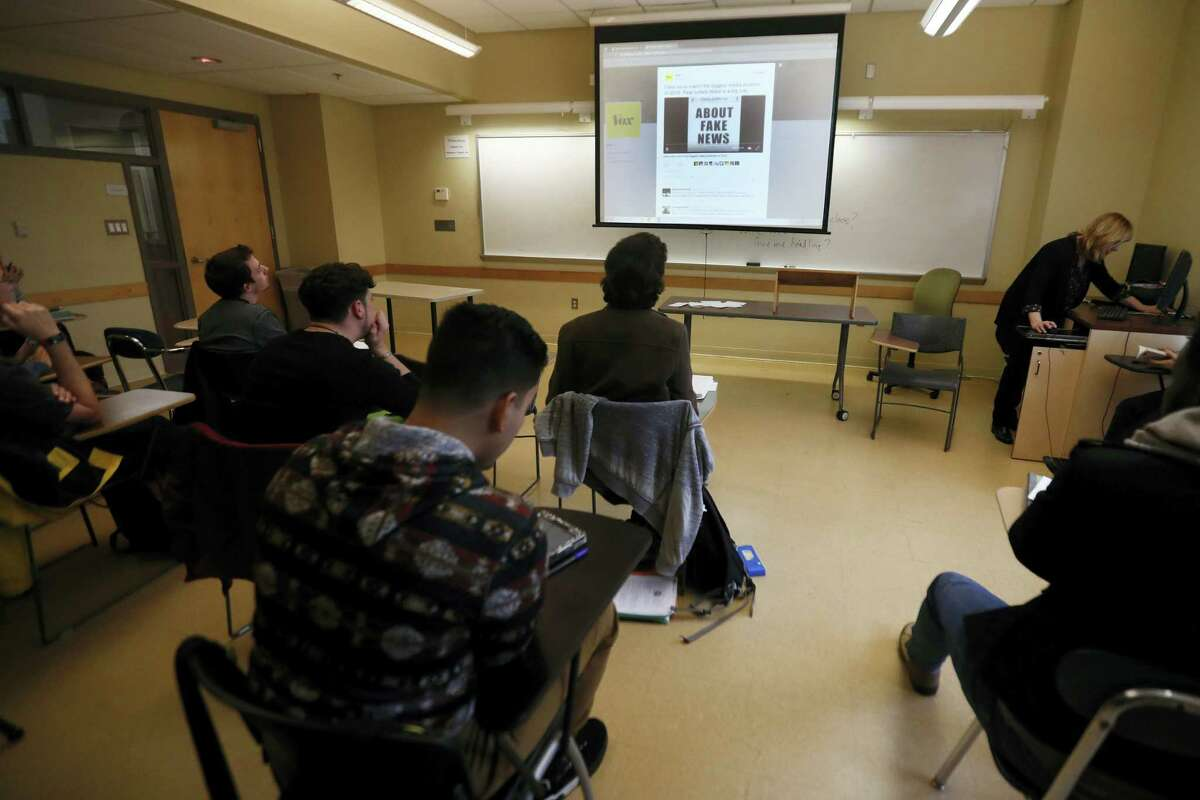 In this Jan. 20, 2017 photo, students in a journalism course at Kean University in Union, N.J., watch a presentation on fake news. Teachers from elementary school through college have been ramping up media literacy training to recognize bogus reports and understand their potential to weaken civic culture.