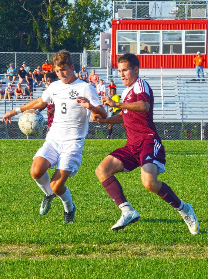EHS sophomore defender Kadin Lieberman, left, shields the ball away from a Dunlap player during the first half of Friday's game in Alton.