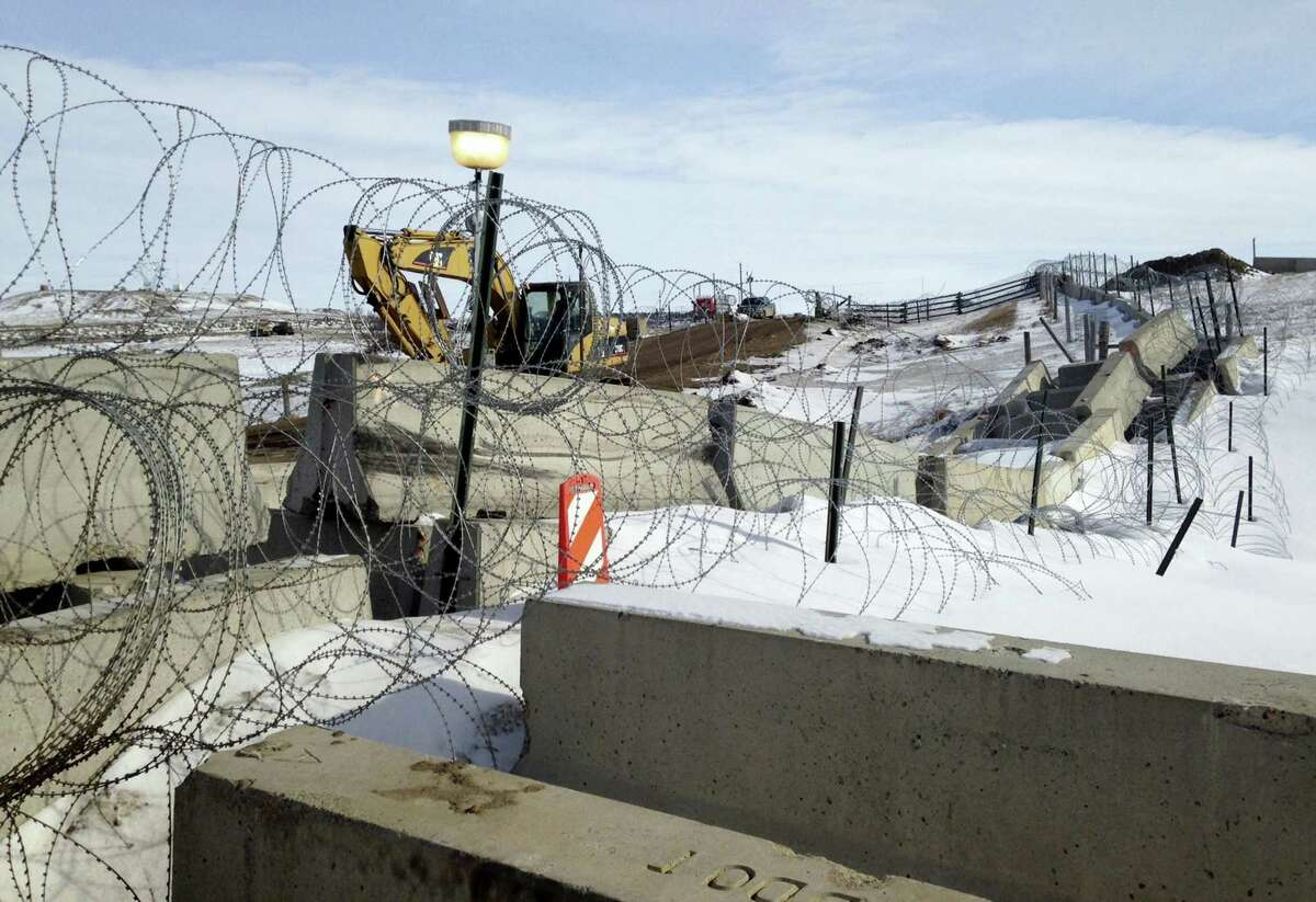 Razor wire and concrete barriers protect access to the Dakota Access pipeline drilling site Thursday near Cannon Ball, North Dakota. The developer says construction of the Dakota Access pipeline under a North Dakota reservoir has begun and that the full pipeline should be operational within three months. One of two tribes who say the pipeline threatens their water supply on Thursday filed a legal challenge asking a court to block construction while an earlier lawsuit against the pipeline proceeds.