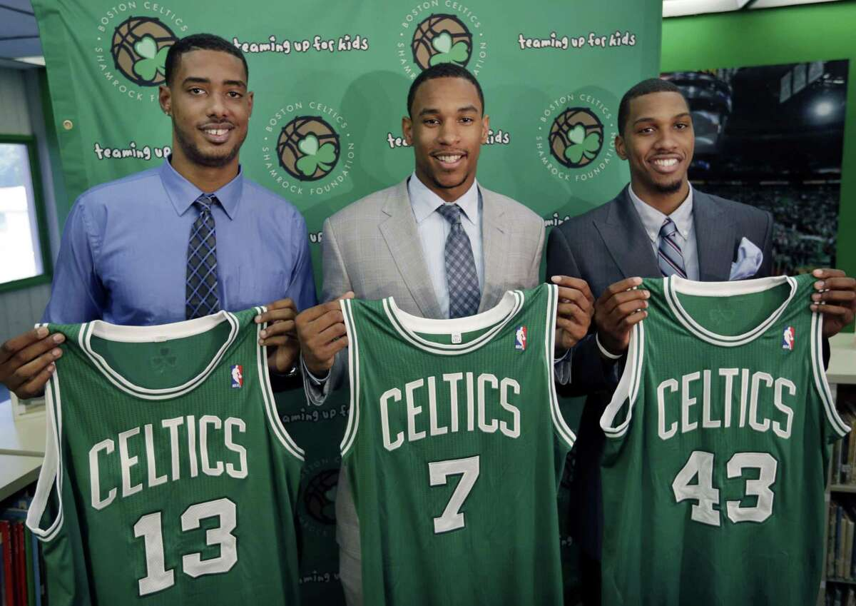 Boston Celtics 2012 draft picks, from left, center Fab Melo and forwards Jared Sullinger and Kris Joseph hold up their jerseys during an introductory NBA basketball news conference in Boston on July 2, 2012.