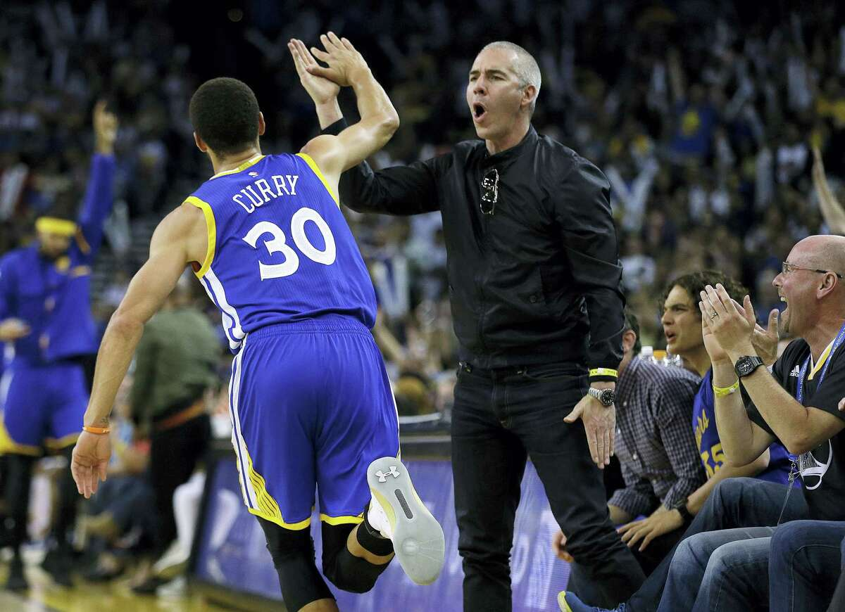 Golden State Warriors' Stephen Curry celebrates with a fan after scoring against the Washington Wizards during the second half of an NBA basketball game on April 2, 2017 in Oakland, Calif.
