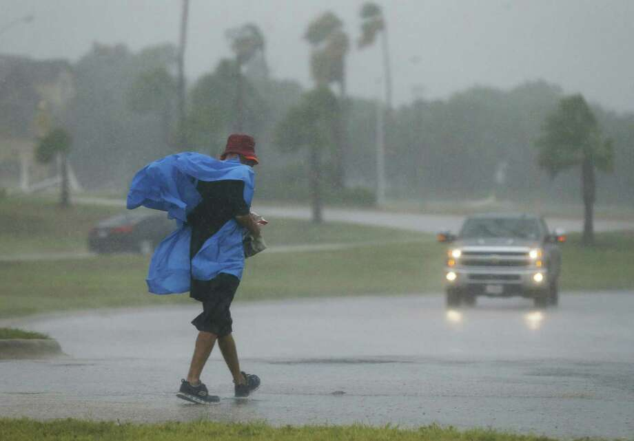 A man's rain gear billows in the winds of Hurricane Harvey as curious Corpus Christi residents come out to Cole Park to see the first stages of the tropical storm whip into the area on Friday, Aug. 25, 2017. (Kin Man Hui/San Antonio Express-News) Photo: Kin Man Hui, Staff / San Antonio Express-News / ©2017 San Antonio Express-News