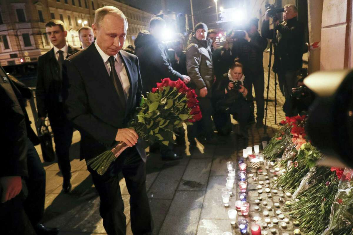 Russian President Vladimir Putin, left, lays flowers at a place near the Tekhnologichesky Institut subway station in St.Petersburg, Russia on April 3, 2017. A bomb blast tore through a subway train deep under Russia's second-largest city Monday, killing several people and wounding many more in a chaotic scene that left victims sprawled on a smoky platform.