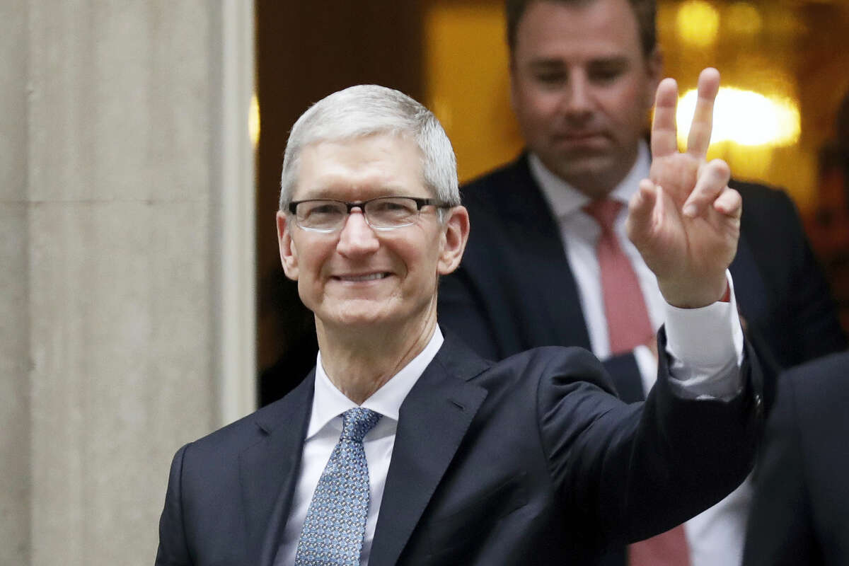 Apple CEO Tim Cook waves at members of the media as he leaves 10 Downing Street in London, Thursday, Feb. 9, 2017.