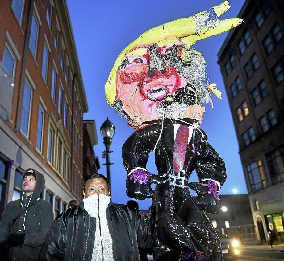 Edgar Sandoval of New Haven carries an effigy of President Donald Trump during a protest against federal immigration policy on Church Street in New Haven last week.  The protest temporarily closed Route 34. Photo: Arnold Gold — New Haven Register File Photo