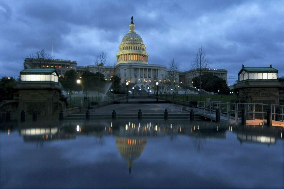 The Capitol is mirrored in a parked car at dawn in Washington, Tuesday, April 4, 2017.