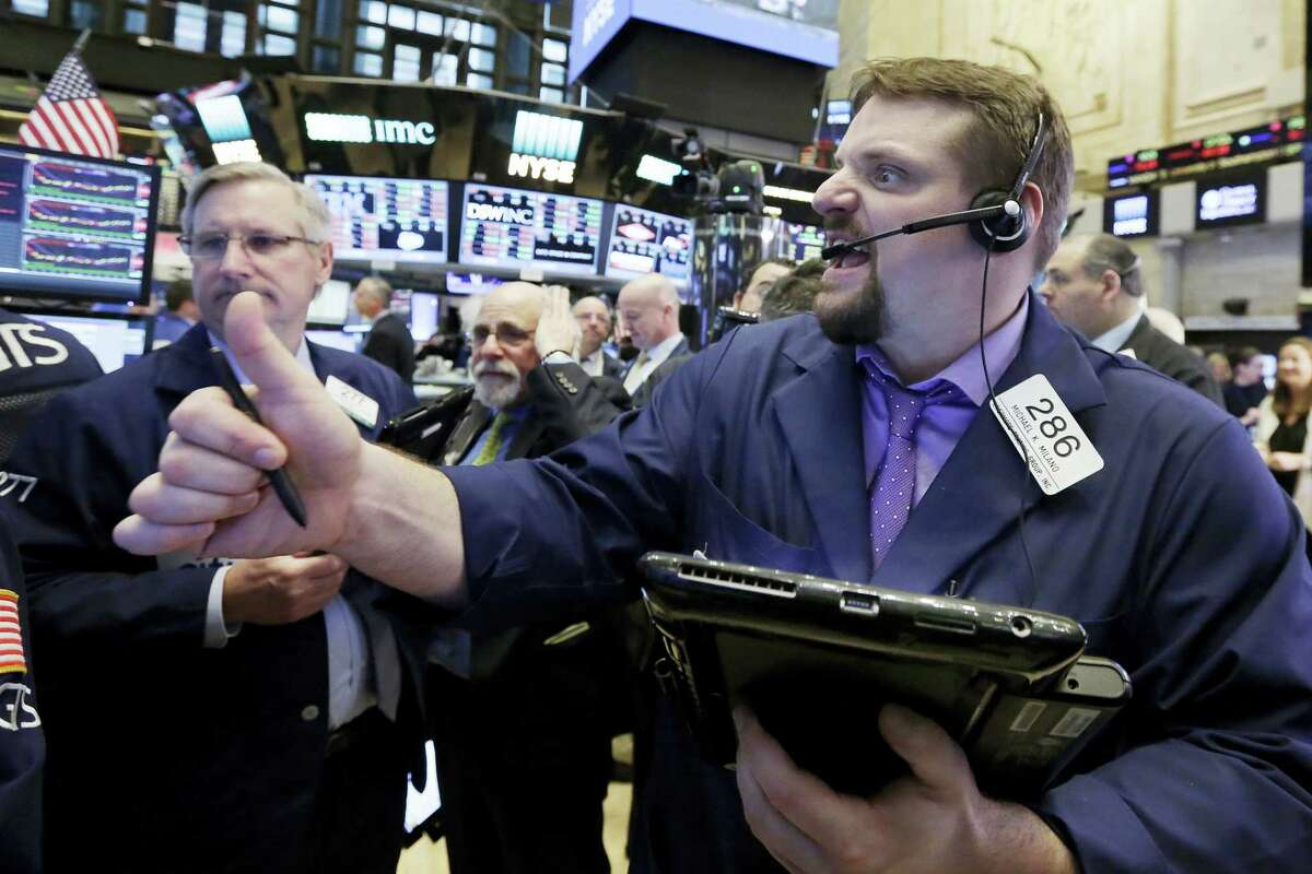 Trader Michael Milano, right, works on the floor of the New York Stock Exchange Tuesday.