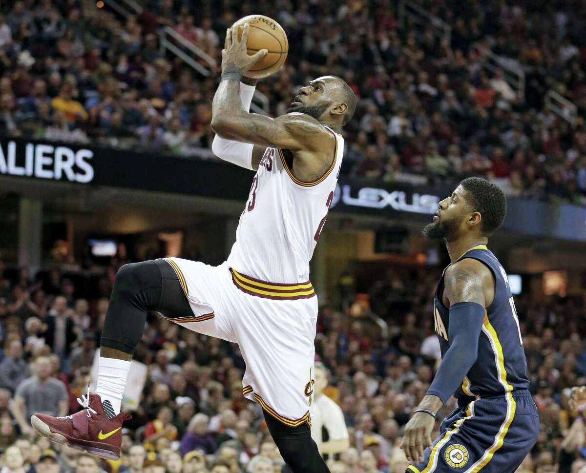 Cleveland Cavaliers' LeBron James, left, drives to the basket against Indiana Pacers' Paul George in the first half of an NBA basketball game Sunday, April 2, 2017 in Cleveland.