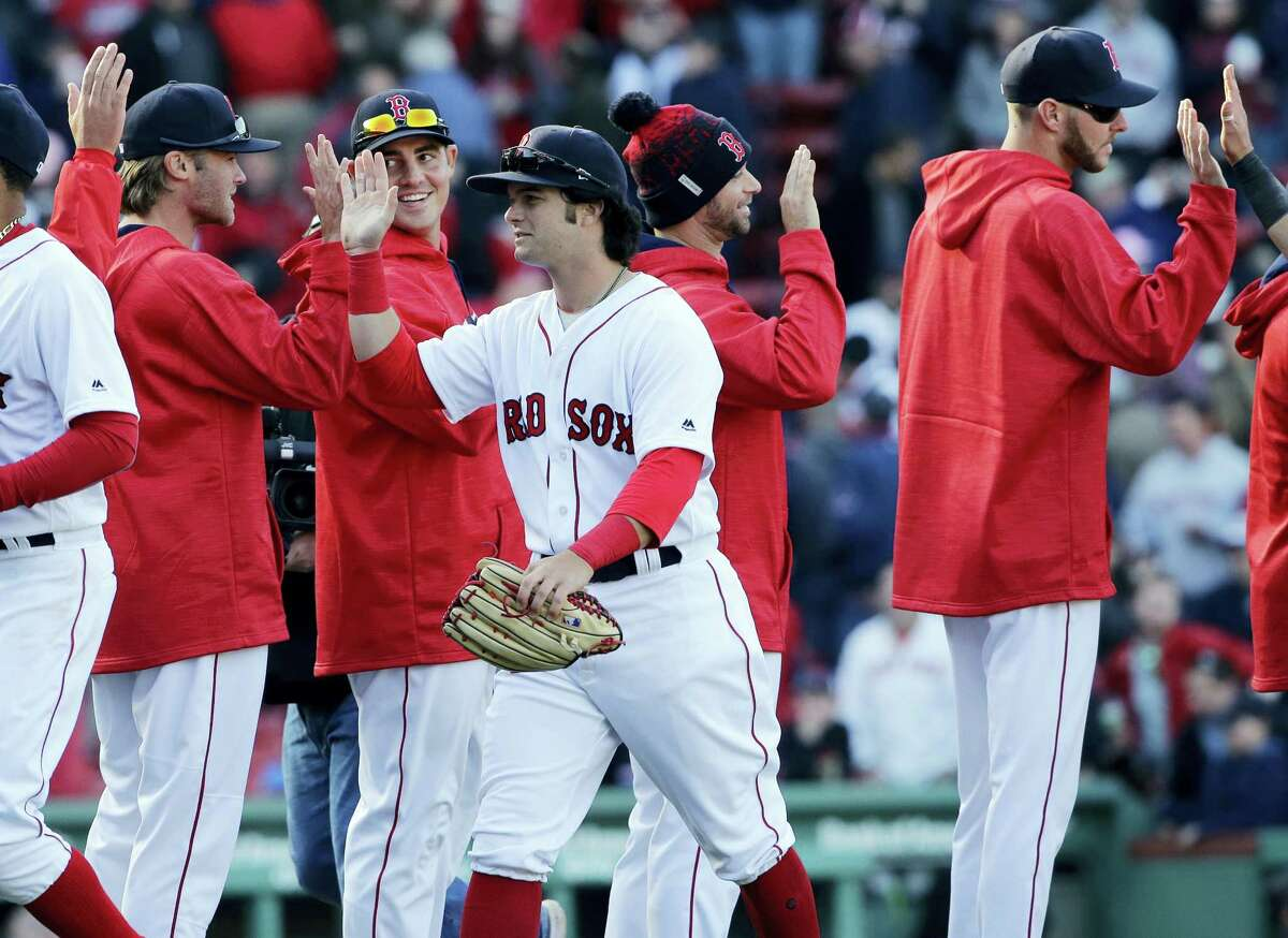 Red Sox outfielder Andrew Benintendi, middle, celebrates with teammates after beating the Pirates on Monday.