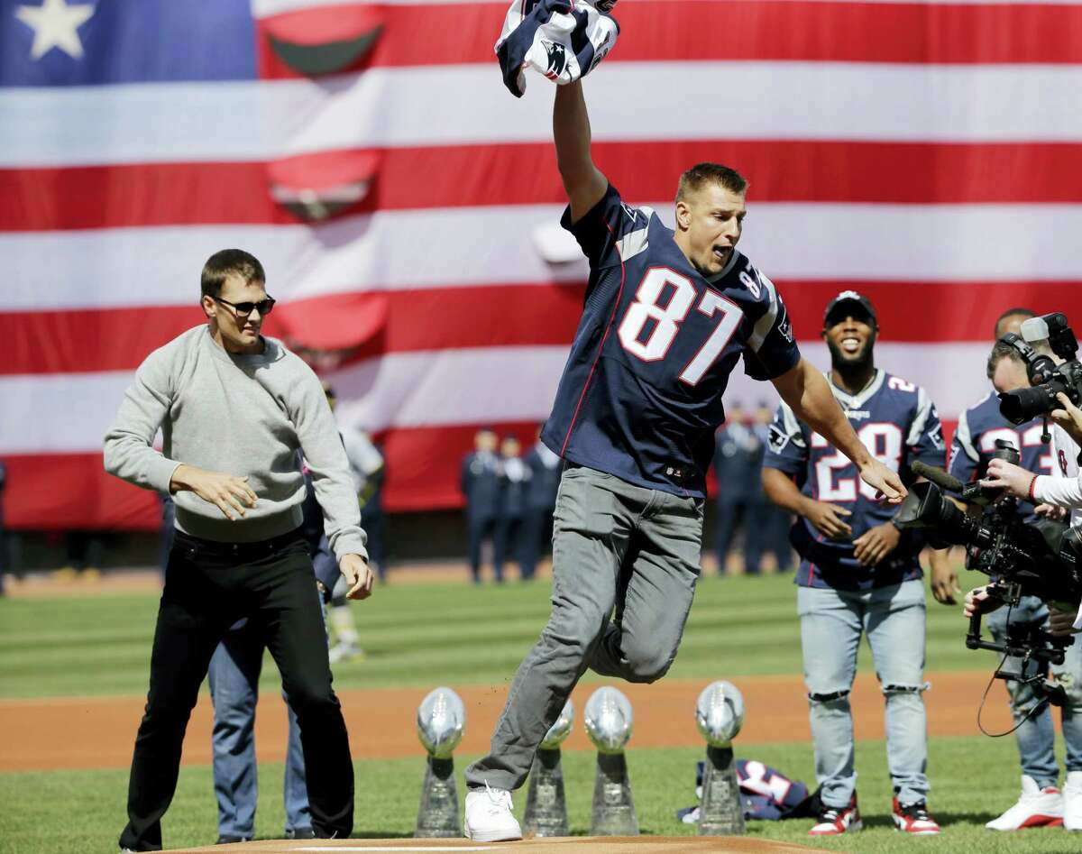 New England Patriots tight end Rob Gronkowski (87) runs with quarterback Tom Brady's recovered Super Bowl jersey as they joke around during Opening Day ceremonies at Fenway Park on Monday.