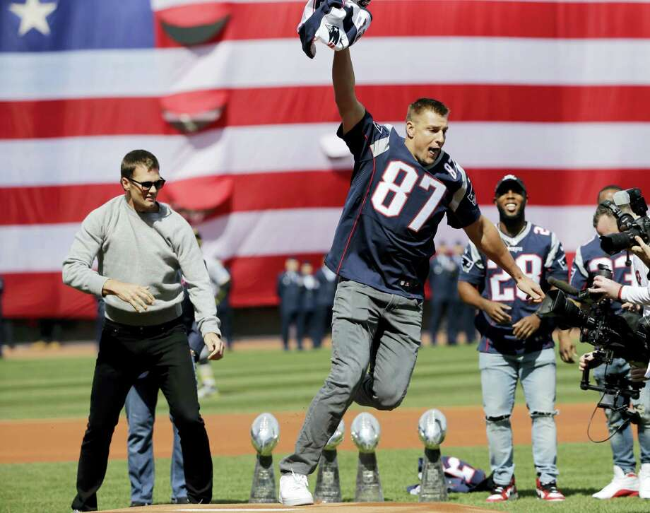 New England Patriots tight end Rob Gronkowski (87) runs with quarterback Tom Brady's recovered Super Bowl jersey as they joke around during Opening Day ceremonies at Fenway Park on Monday. Photo: Elise Amendola — The Associated Press  / Copyright 2017 The Associated Press. All rights reserved.