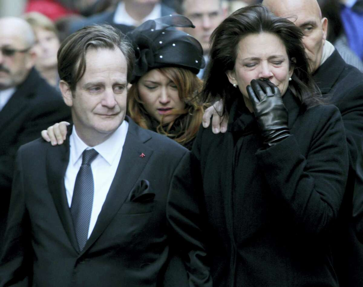 Matthew Badger, left, and ex-wife Madonna Badger, parents of three girls killed along with their maternal grandparents in a Christmas morning fire in Stamford, Conn., react as caskets are carried into a church during a funeral in New York in 2012. A charity that Matthew Badger started announced Thursday, Feb. 9, 2017, that he had died at age 51.