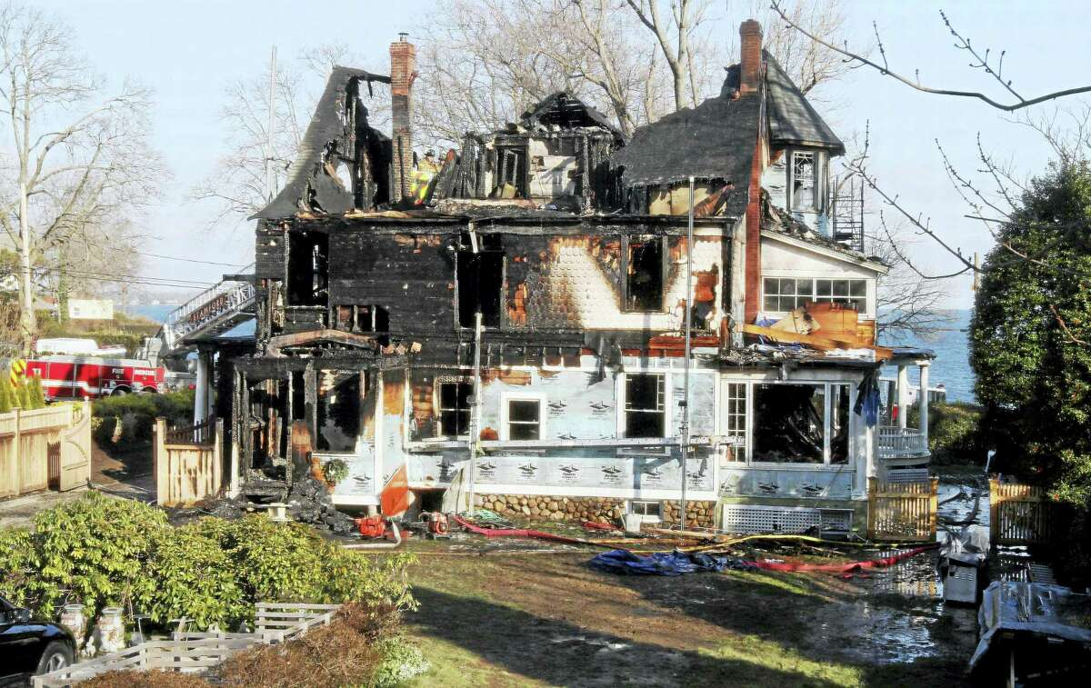 Firefighters investigate a house in Stamford where an early morning fire left five people dead in 2011.