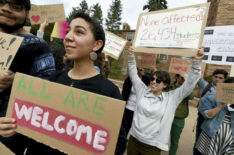 Gwendalynn Roebeke, left, is among dozens of people at a travel ban protest at the University of Colorado in Boulder on Thursday Photo: Cliff Grassmick — Daily Camera Via AP / (C) 2012 Boulder Daily Camera, MediaNews Group, Prairie Mountain Publishing http://www.dailycamera.com/ http://www.buffzone.com/