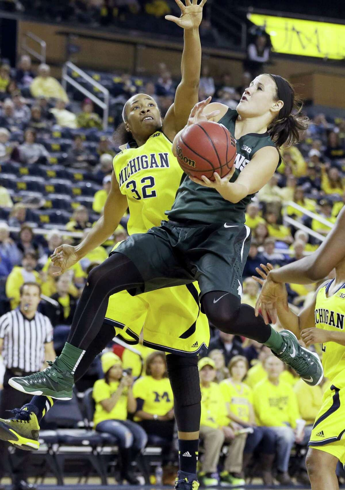 Michigan State guard Tori Jankoska, right, makes a layup while defended by Michigan forward Kelsey Mitchell (32) during the second half of an NCAA college basketball game in Ann Arbor, Mich. on Jan. 4, 2015. Michigan defeated Michigan State 74-65.