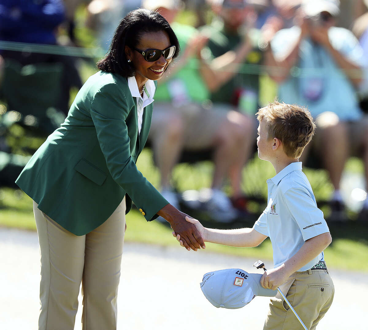Carter Kontur, right, shakes hands with former Secretary of State Condoleezza Rice after putting on the 18th green during the Drive Chip & Putt finals at Augusta National on Sunday.