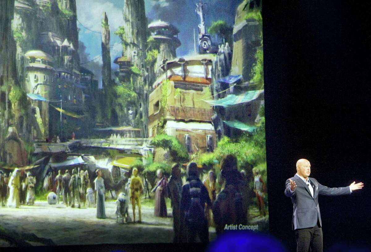 In this Saturday, Aug. 15, 2015, file photo, Bob Chapek, chairman of Walt Disney Parks and Resorts, speaks in front of concept art of the newly announced Star Wars Land at the D23 Expo in Anaheim, Calif. Disney CEO Bob Iger said Tuesday, Feb. 7, 2017, the company will open its Star Wars-themed lands at California's Disneyland and Florida's Walt Disney World in 2019.