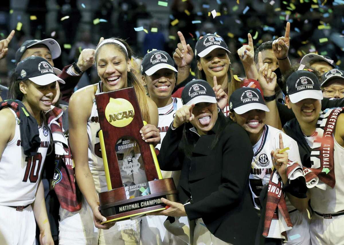 South Carolina forward A'ja Wilson holds the trophy and coach Dawn Staley points as the team celebrates their win over Mississippi State in the national championship game Sunday in Dallas.