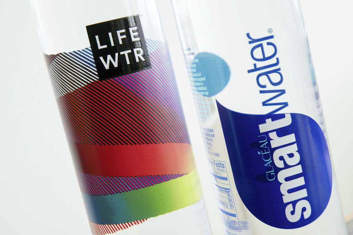 """Bottles of Lifewtr and Smartwater are displayed in Philadelphia. As bottled water surges in popularity, Coke, Pepsi and other companies are using celebrity endorsements, stylish packaging and fancy filtration processes like """"reverse osmosis"""" to sell people on expanding variations of what comes out of the tap."""