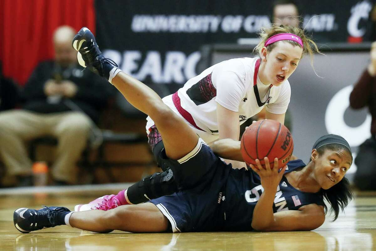 Connecticut's Crystal Dangerfield (5) dives for a loose ball against Cincinnati's Sam Rodgers during the first half Tuesday in Cincinnati. The Huskies won 96-49 for their 98th consecutive win.