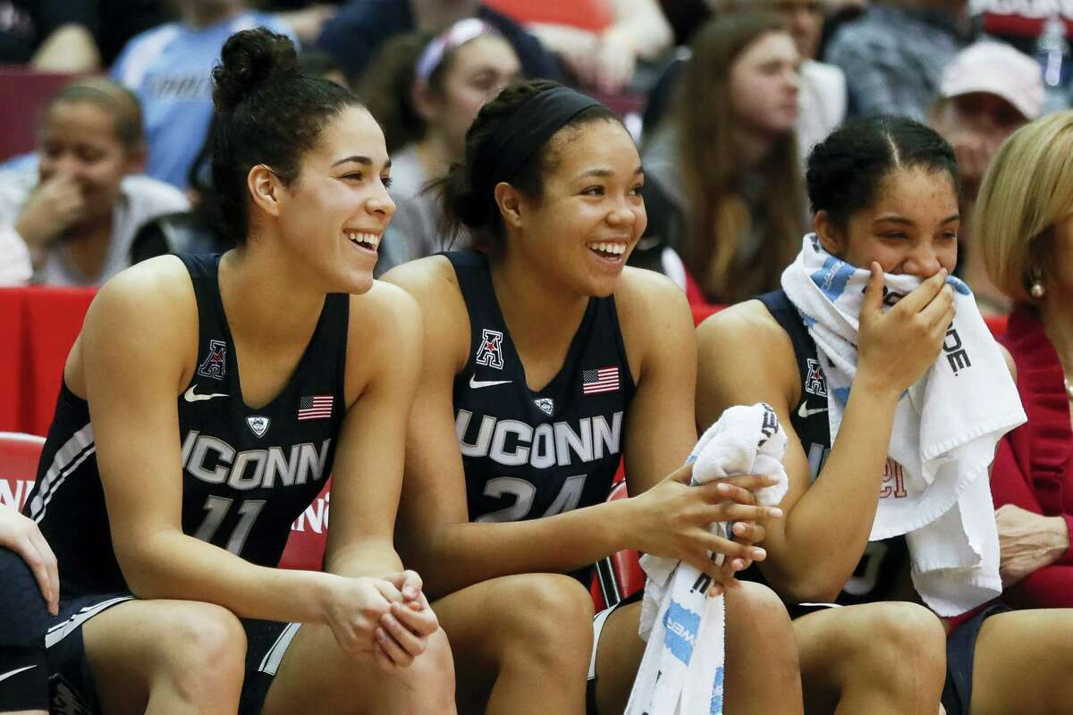 UConn's Kia Nurse (11), Napheesa Collier (24), and Gabby Williams, right, smile on the bench in the second half of the team's 96-49 victory over Cincinnati.