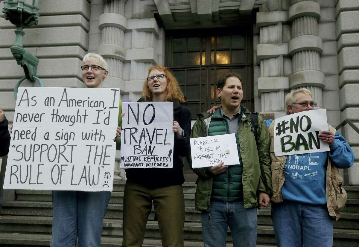 Kay Aull, from left, holds a sign and chants with Beth Kohn, Paul Paz y Mino and Karen Shore outside of the 9th U.S. Circuit Court of Appeals in San Francisco, Tuesday, Feb. 7, 2017.