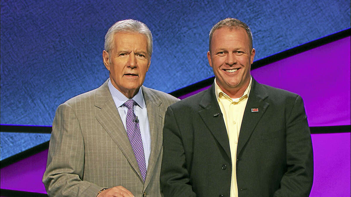 Photo Courtesy: Jeopardy Productions, Inc. Warren Toland of Torrington, right, is joined by Jeopardy! host Alex Trebek. Toland placed second in his appearance on the game show on Thursday, Feb. 2.