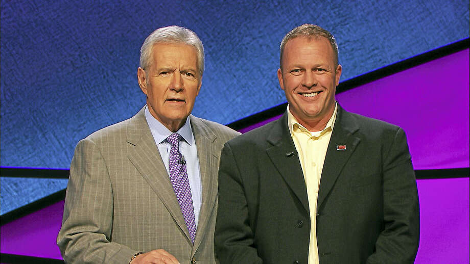 Photo Courtesy: Jeopardy Productions, Inc. Warren Toland of Torrington, right, is joined by Jeopardy! host Alex Trebek. Toland placed second in his appearance on the game show on Thursday, Feb. 2. Photo: Digital First Media