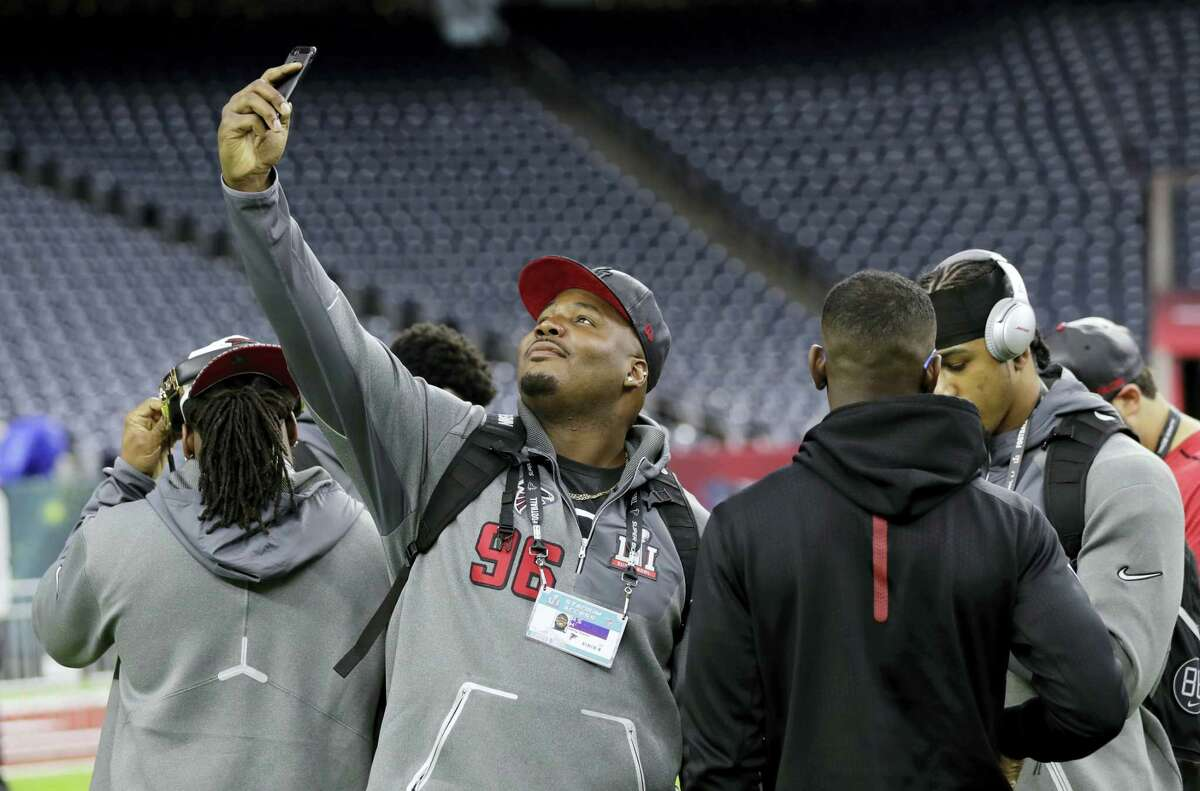 Atlanta Falcons' Jimmy Staten center, takes photos during a walk through with teammates at NRG Stadium on the eve of the NFL Super Bowl 51 football game on Feb. 4, 2017 in Houston. Atlanta will face the New England Patriots in the Super Bowl Sunday.