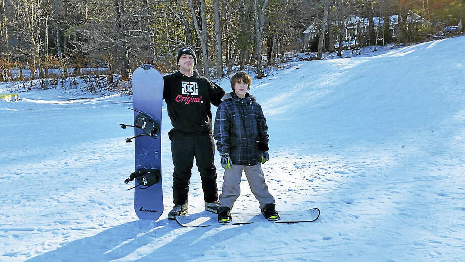 Christopher Carbone of Torrington and his son Christopher, Jr., 12, practiced their snowboarding at the snow slope at the ninth Annual Winter Carnival at Major Besse Park in Torrington on Saturday. Photo: N.F. Ambery — The Register Citizen