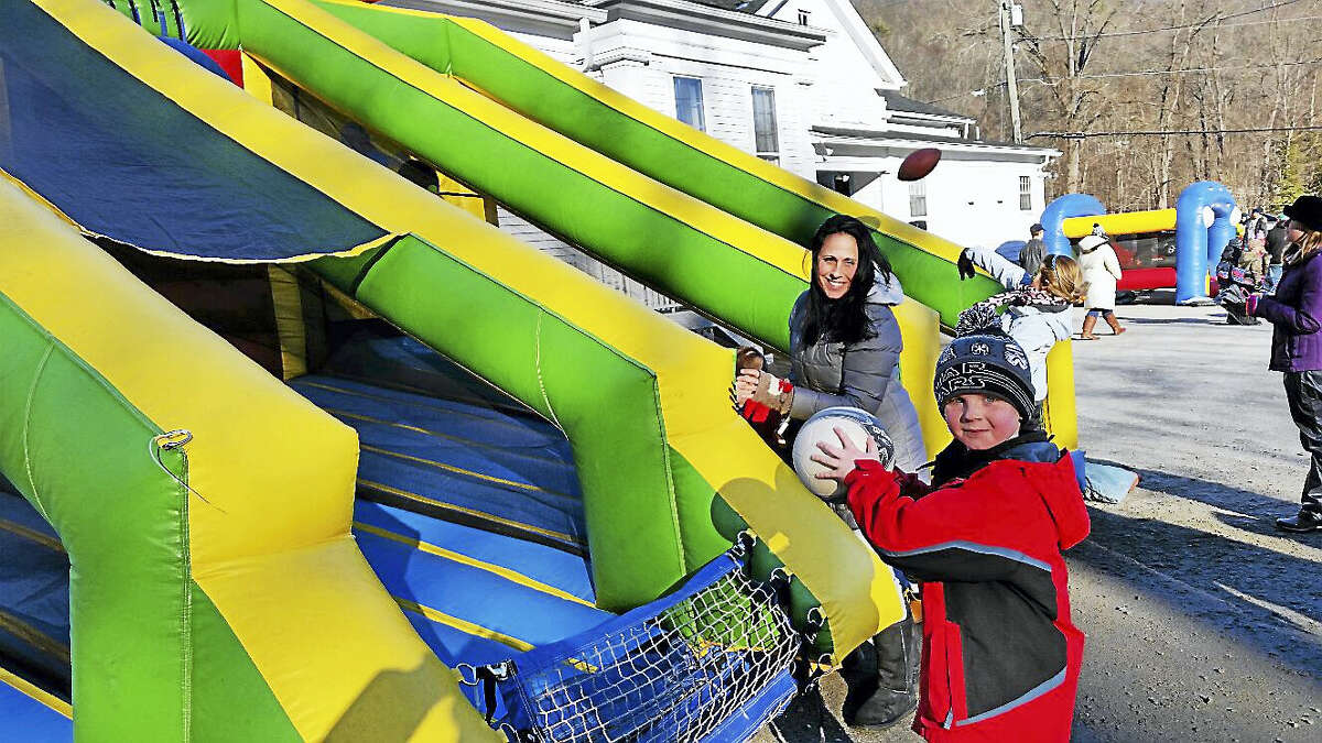 Nathan Gryniuk, 7, of Torrington practiced soccer throws while supervised by his mother Sue Gryniuk at an inflated sports bounce house at the ninth Annual Winter Carnival at Major Besse Park.