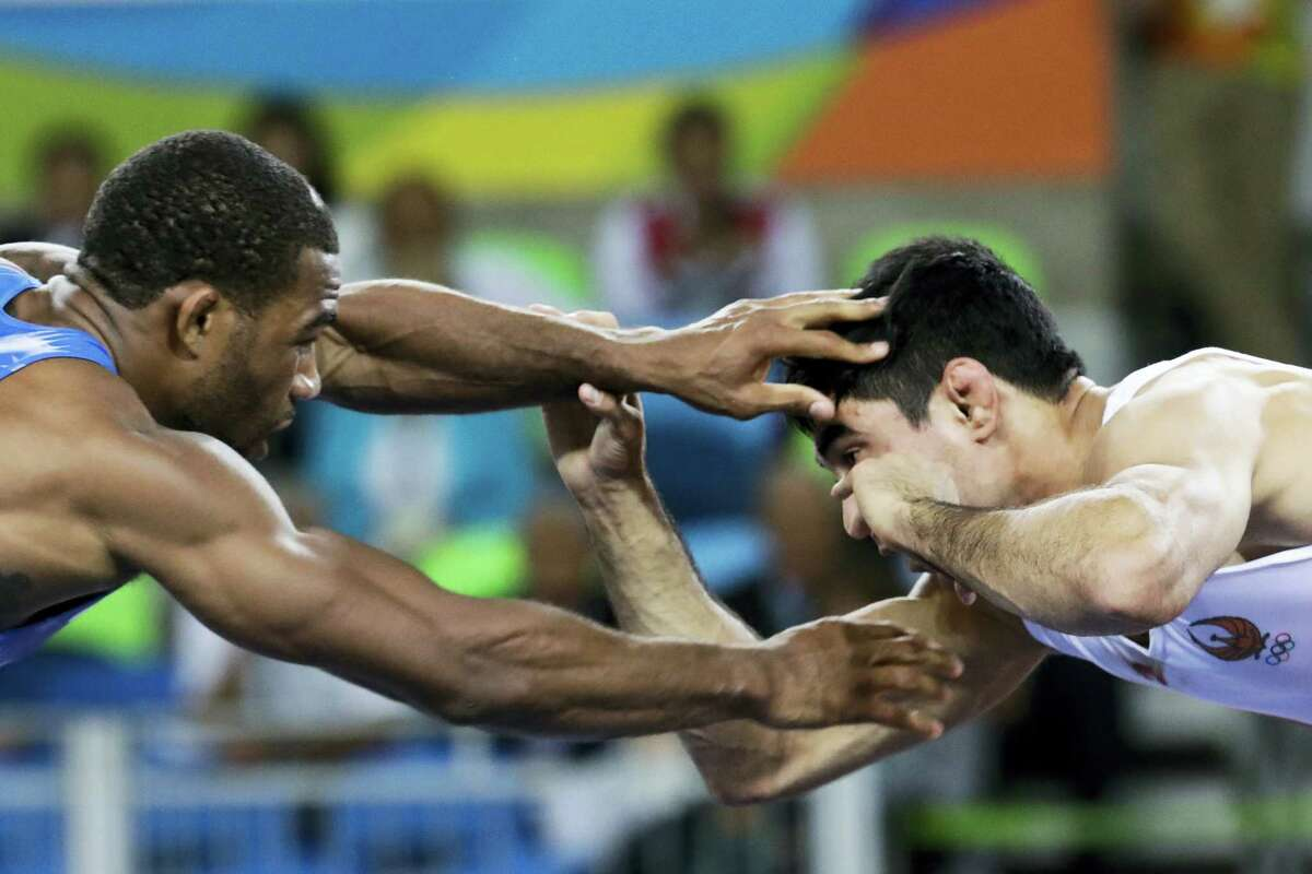 United States' Jordan Ernest Burroughs, left, competes against Uzbekistan's Bekzod Abdurakhmonov during the men's 74-kg freestyle wrestling competition at the 2016 Summer Olympics in Rio de Janeiro, Brazil. Iran on Friday banned U.S. wrestlers from this month's Freestyle World Cup in response to President Donald Trump's executive order forbidding visas for Iranians, the official IRNA news agency reported.