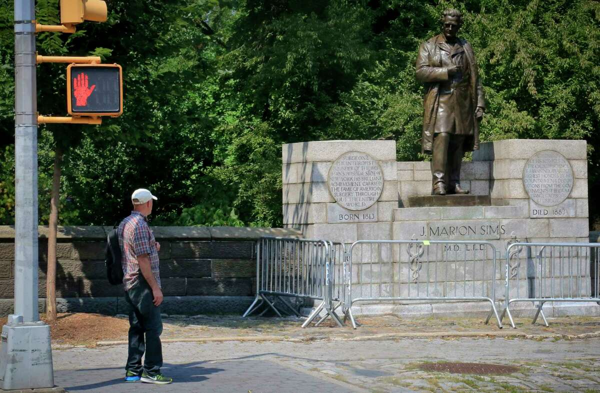 FILE- In this Aug. 22, 2017 file photo, a man looks at a statue in New York's Central Park statue honoring Dr. J. Marion Sims, known as the ?