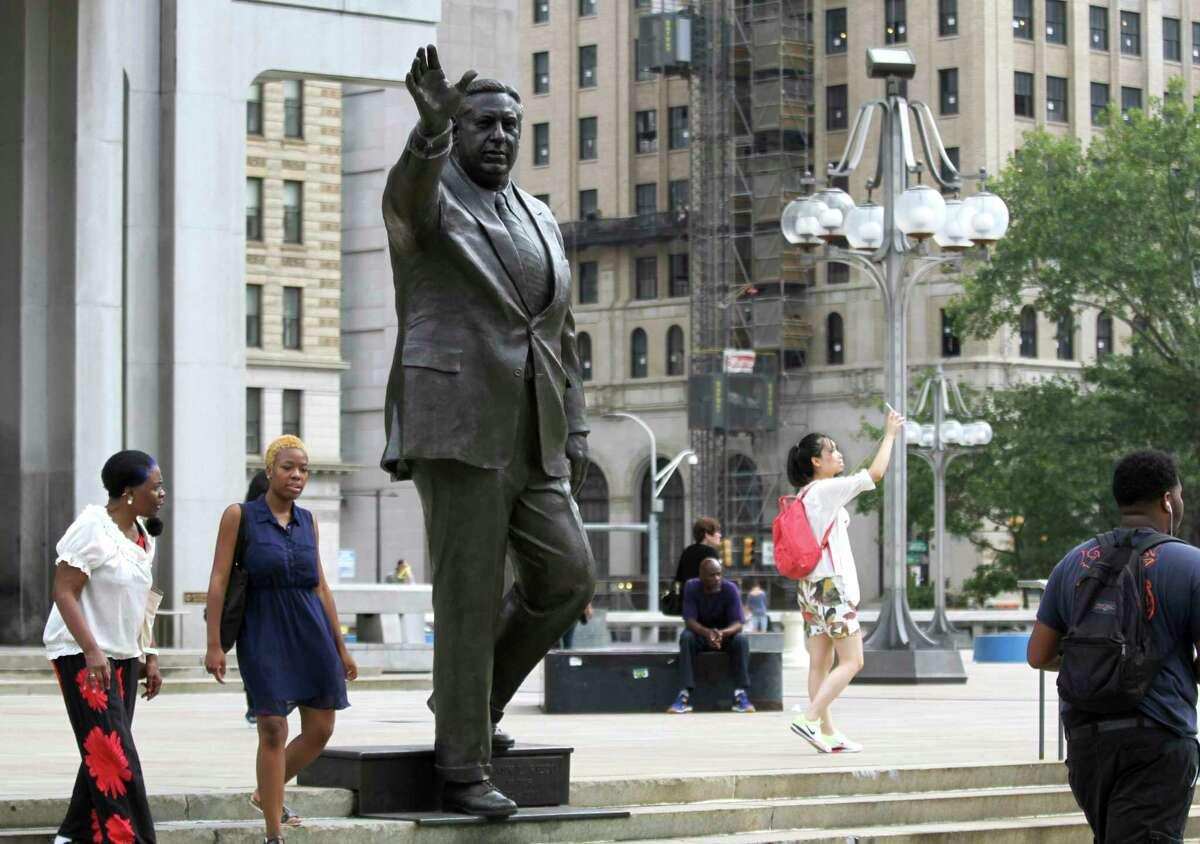FILE- In this Aug. 10, 2016 file photo, people walk by a statue of late Philadelphia Mayor Frank Rizzo, who also served as the city's police commissioner, on Thomas Paine Plaza outside the Municipal Services Building in Philadelphia. A city councilwoman is leading the push to take down the likeness of Rizzo, considered by some as a tough-talking, tougher-on-crime lawmaker, but to others as a racist, anti-gay bigot. (AP Photo/Dake Kang, File) ORG XMIT: NYR403