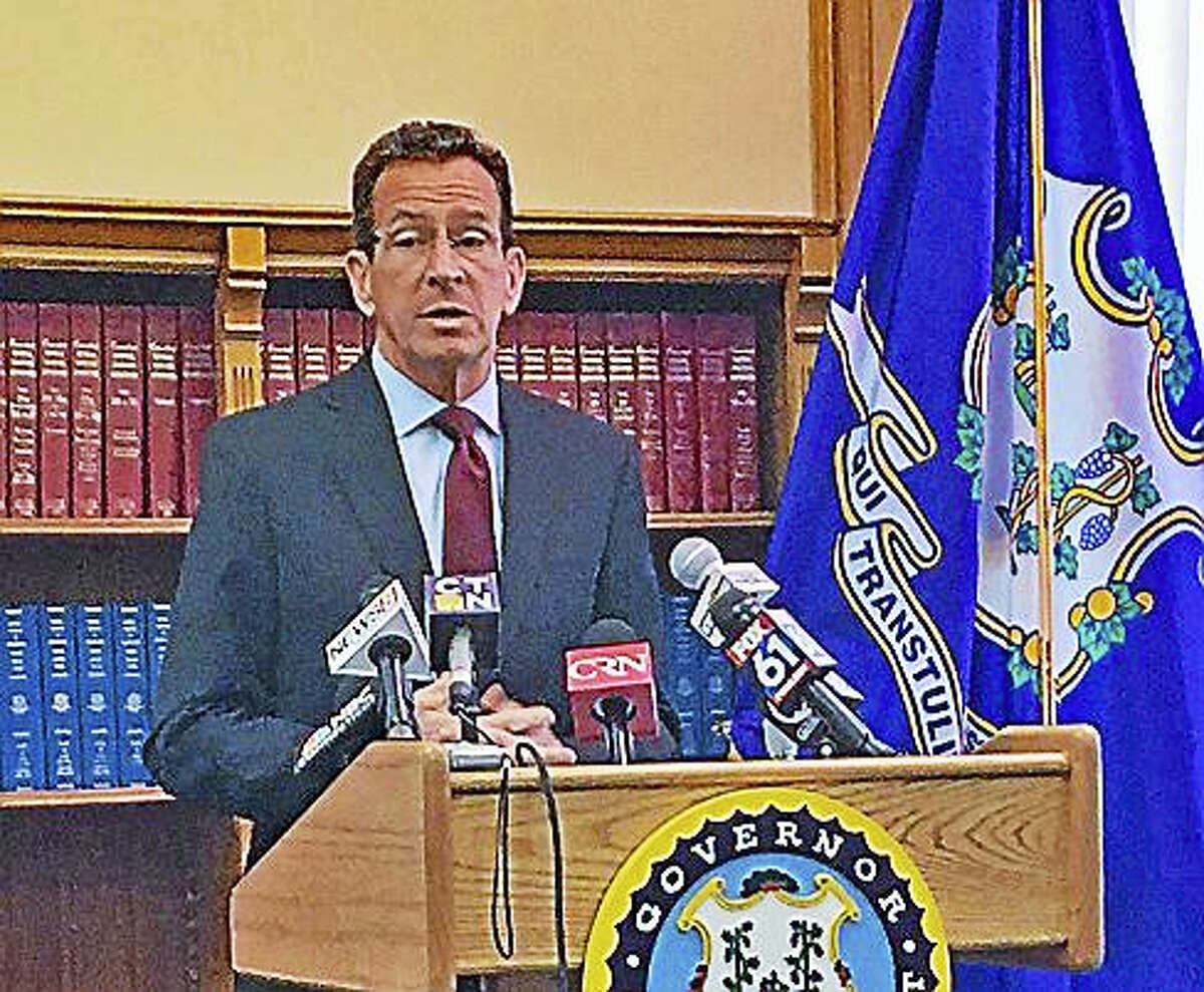 Gov. Dannel P. Malloy speaks with reporters Friday at the state Capitol in Hartford.