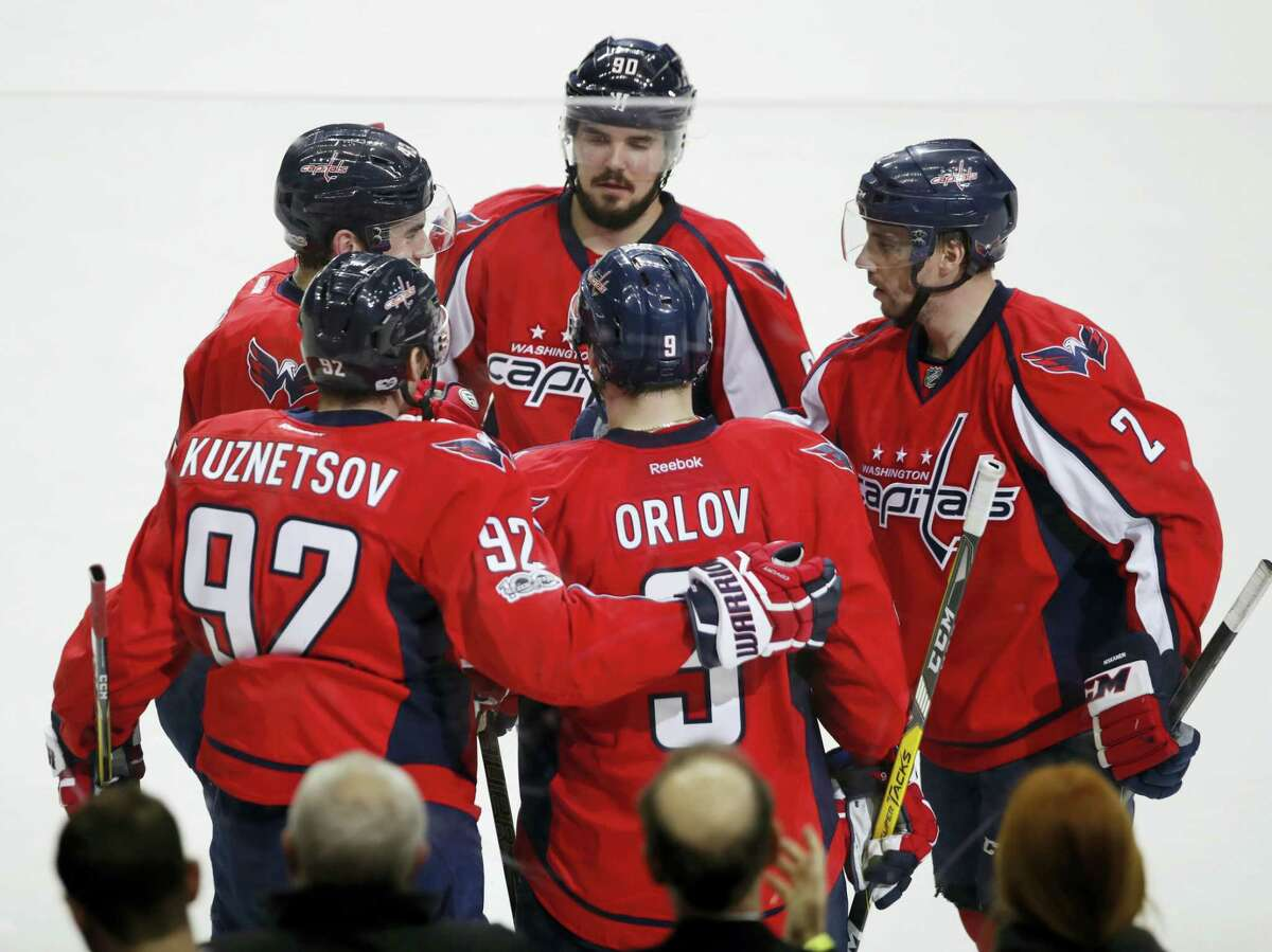 Washington Capitals center Evgeny Kuznetsov (92) of Russia is congratulated by his teammates Dmitry Orlov (9) also of Russia, Matt Niskanen (2), Marcus Johansson (90) of Sweden, and Tom Wilson (43) after scoring the fifth and final goal during the third period of an NHL hockey game in Washington, Wednesday, Feb. 1, 2017. The Capitals won 5-3. (AP Photo/Manuel Balce Ceneta)