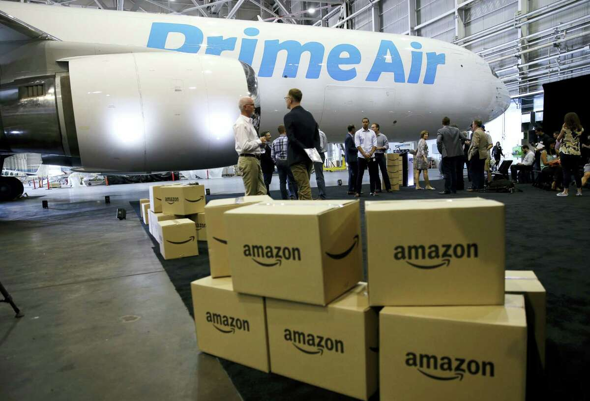 """Amazon.com boxes are shown stacked near a Boeing 767 Amazon """"Prime Air"""" cargo plane on display in a Boeing hangar in Seattle."""