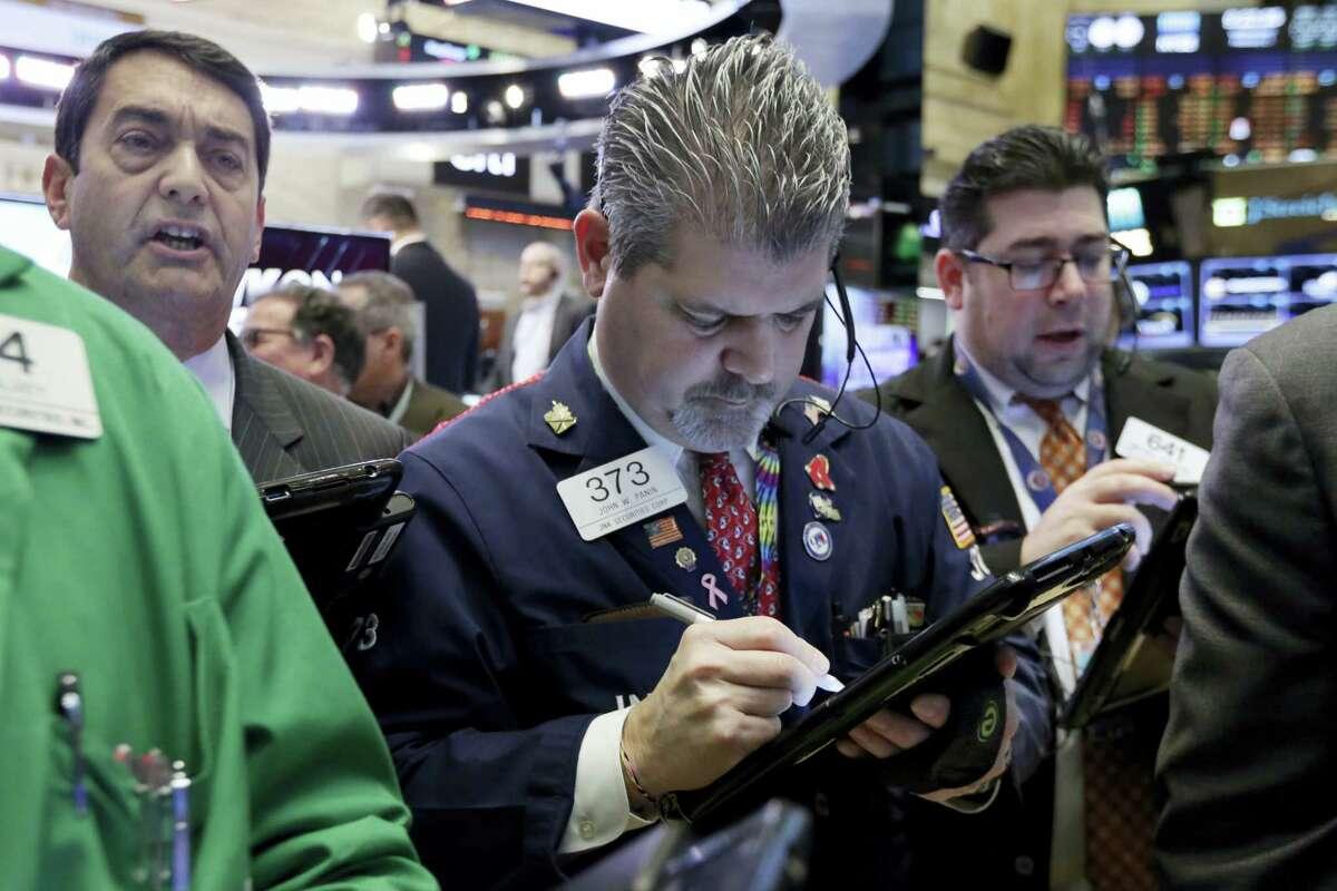 Trader John Panin, center, works on the floor of the New York Stock Exchange Wednesday.