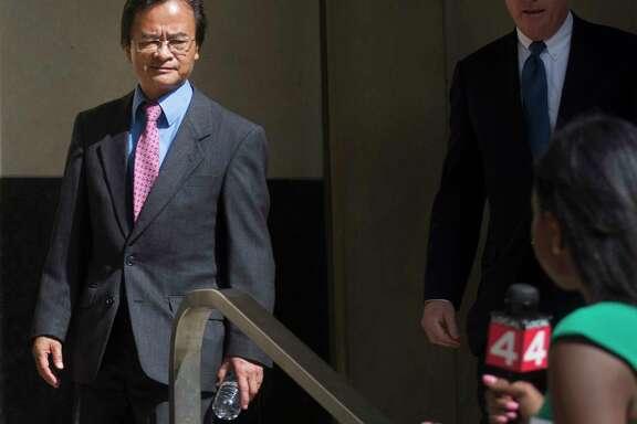 Volkswagen engineer James Robert Liang, left, leaves court in Detroit in 2016. He was sentenced to prison on Friday.