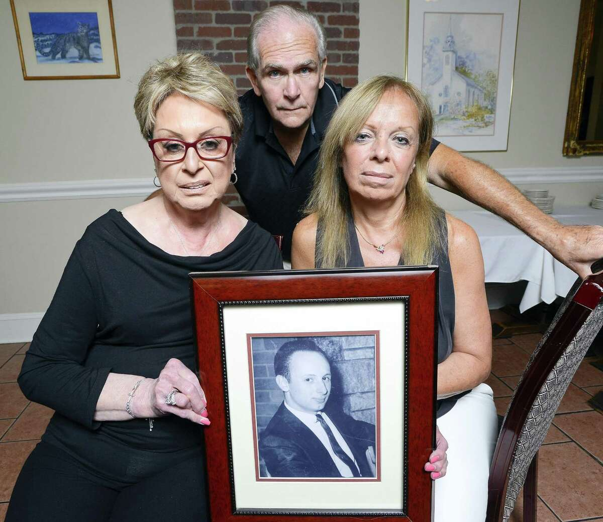 """Toni Lupinacci, Fran Gross, and brother-in-law, Anthony """"Butch"""" Lupinacci are photograph on August 23, 2017 with a portrait of Joe Pellicci at the family's restaurant on Stamford's Westside. Pellicci, shown in a portrait photograph taken around 1961 that hangs in the entrance way of Pellicci's Restaurant, was killed in 1973 in one of Stamford's most notorious murders, that remains still unsolved. They hope a soon-to-be-made TV show about the cold case prompts Stamford police to reopen it."""