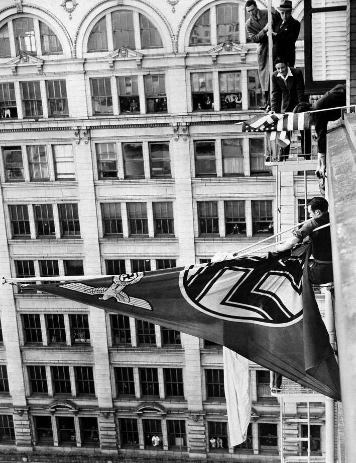 Youths remove the German swastika flag from pole of German consulate in San Francisco on Jan. 19, 1941. Two U.S. Navy sailors were turned over to Navy officials in connection with the episode. (AP Photo) Photo: ASSOCIATED PRESS