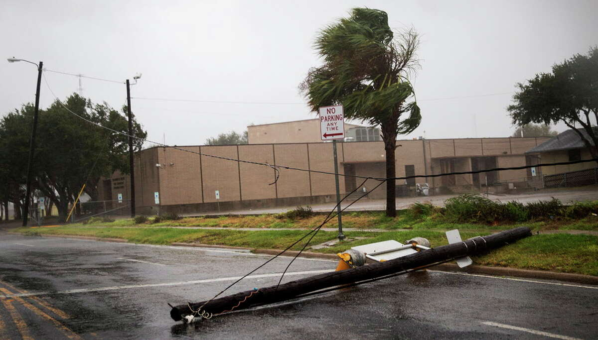 A power pole lays in the middle of a street as Hurricane Harvey makes landfall in Corpus Christi, Texas, on Friday, Aug. 25, 2017. Hurricane Harvey smashed into Texas late Friday, lashing a wide swath of the Gulf Coast with strong winds and torrential rain from the fiercest hurricane to hit the U.S. in more than a decade. (Nick Wagner/Austin American-Statesman via AP)