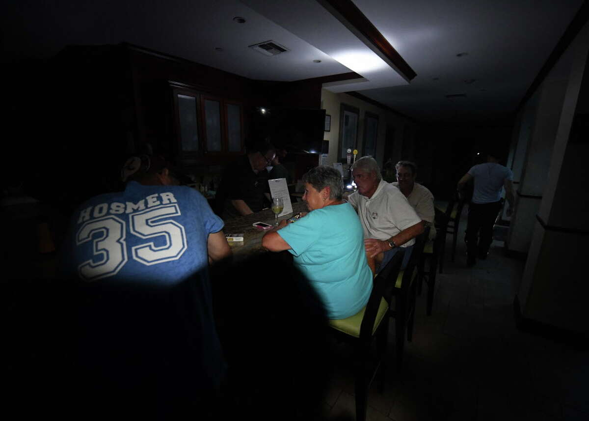 Local residents sit at the bar in the dark after a citywide power failure as Hurricane Harvey hit Corpus Christi, Texas, on August 25, 2017. Harvey on Friday further intensified into a dangerous category four storm, just hours before it was due to slam into the Texas coast, US meteorologists said. / AFP PHOTO / MARK RALSTONMARK RALSTON/AFP/Getty Images