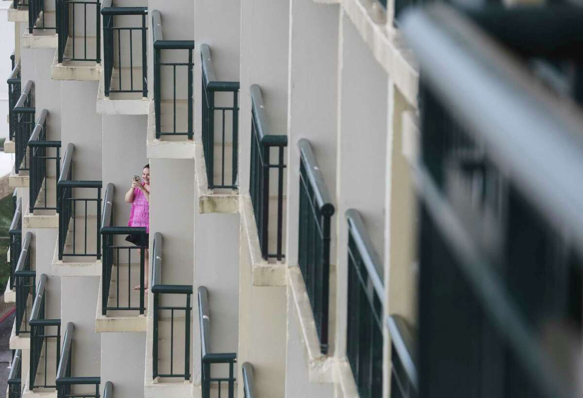 A guest staying at The San Luis Resort excitingly taking a photograph of the Gulf of Mexico from her balcony hours before Hurricane Harvey is scheduled to make landfall Friday, Aug. 25, 2017, in Galveston.